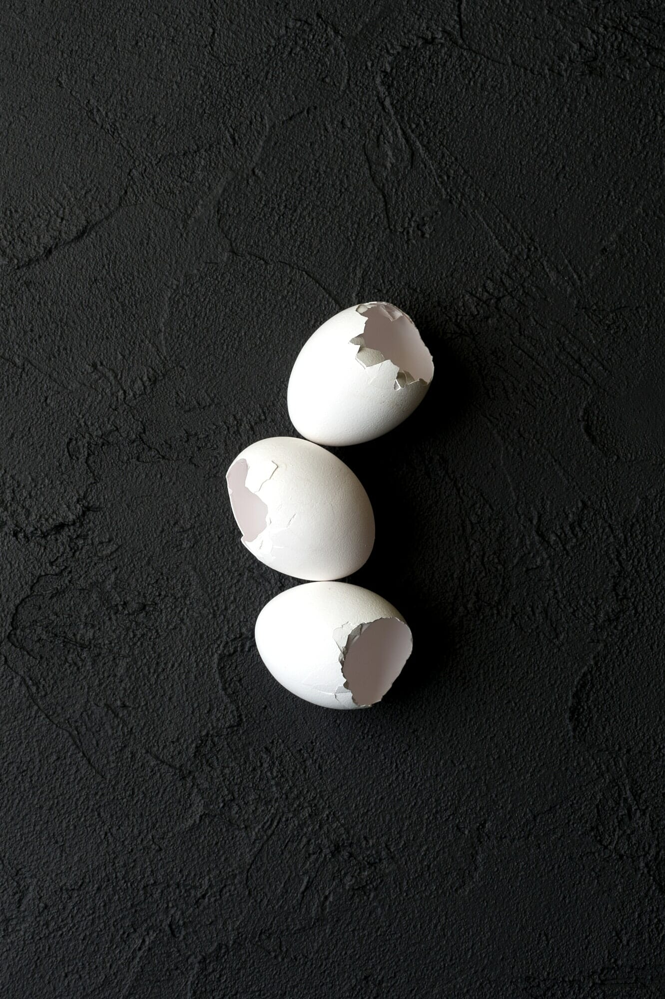 Shell from white chicken eggs on a black textured background.
